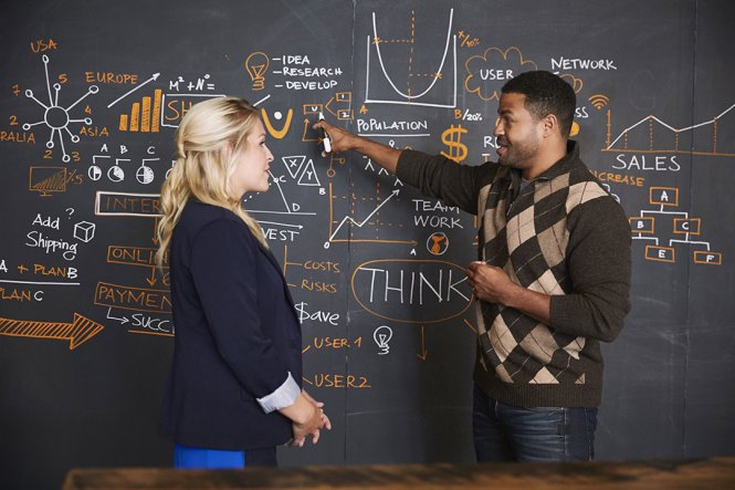 A man and a woman in front of a blackboard with equations on it.