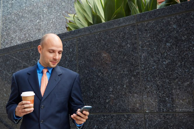 Professional man looks at smartphone.