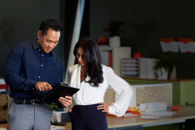 A man and woman using a tablet while standing up.