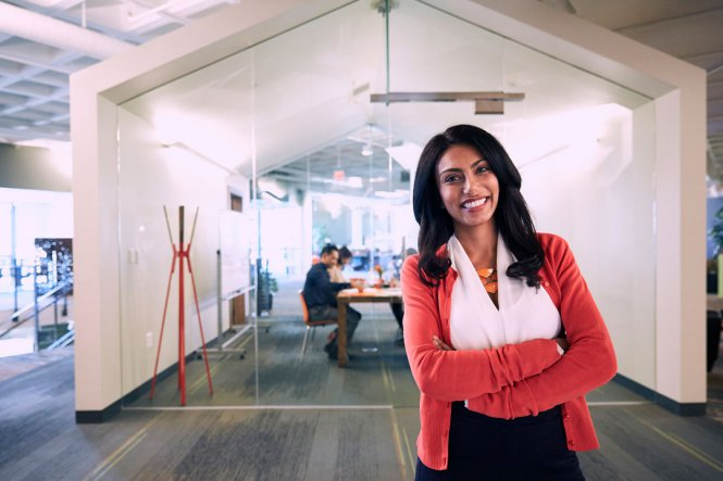 A smiling woman in a modern office space.