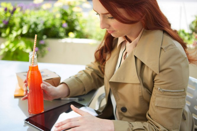 A woman sitting at a table outside, drinking a soda and using a tablet.