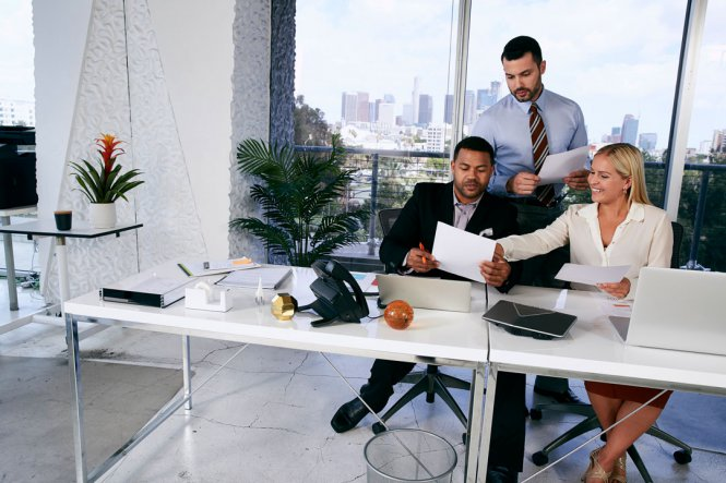 Two men and a woman reviewing documents in an office.