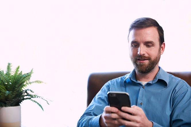 A man sitting at a desk, using a smartphone.