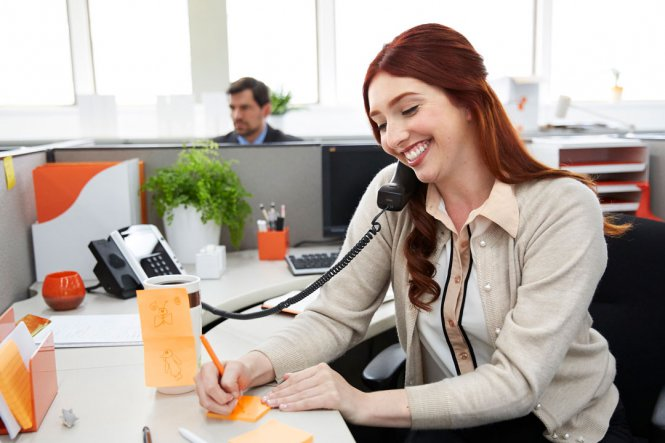 A smiling woman talking on an office telephone.