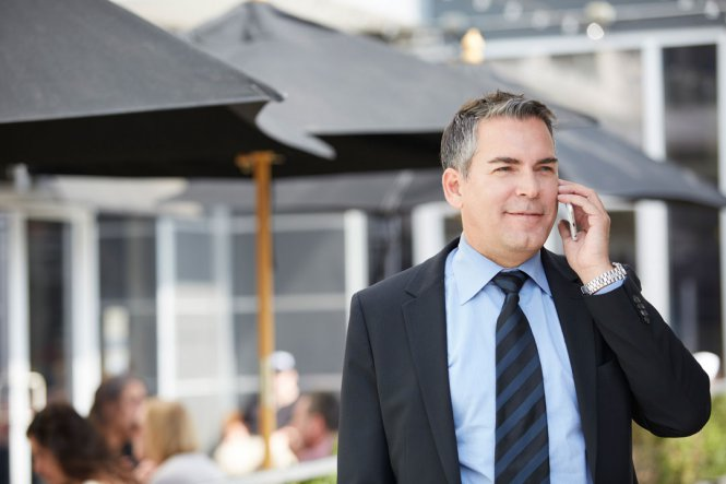 A man in a suit talking on a mobile phone, outside of a restaurant.