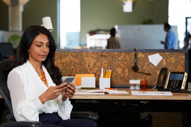 A woman using a smartphone while sitting at her desk.