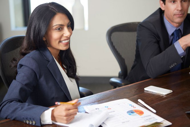 A smiling woman in a suit, sitting as a table in a conference room.