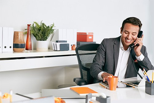 A smiling man talking on an office telephone while seated at a desk.