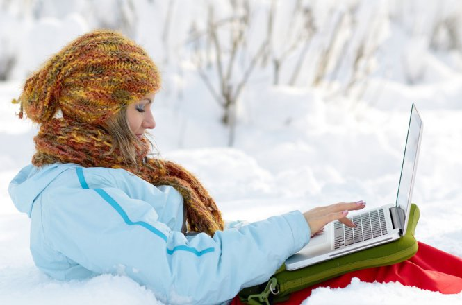 Young woman outside in snow using laptop.