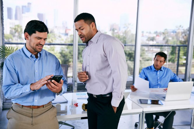 Two men talking in an office, with one of them using a smartphone.