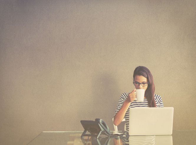 A woman works from home and drinks coffee at a desk.