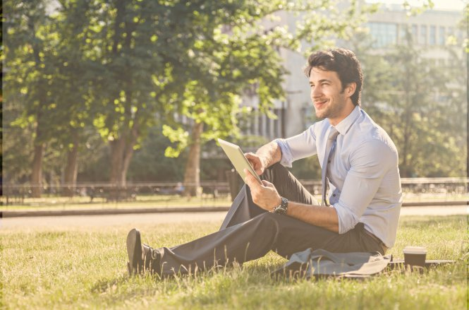 A man in a suit sitting in a park on a nice day, using a tablet.