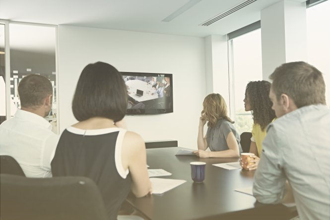 Colleagues sitting at a conference table, viewing a screen during a video conference.