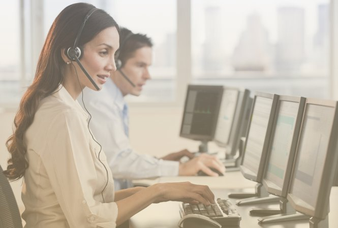 A man and a woman working at a call center, talking on headsets while using their computers.