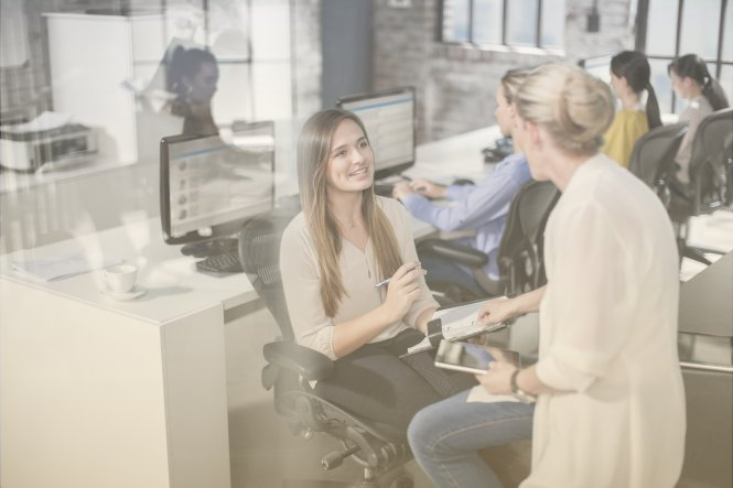 Two women enjoying agility in the workplace by having a chat in their open office.