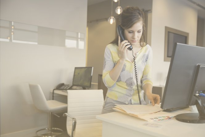 How does SIP trunking work? A woman uses her office phone to call another branch.