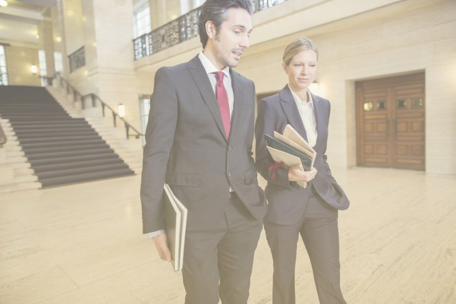 Two lawyers who use law firm billing solutions walking through a courthouse