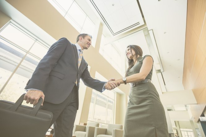 A businessman and woman shakes hands and discuss the challenges of recruitment and selection