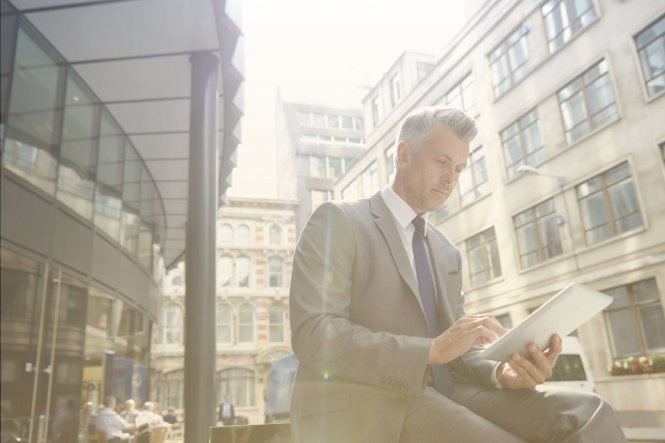 A suited man uses a tablet with an insurance agency BYOD policy.