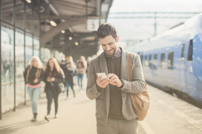 Man on a train platform receives a meeting reminder SMS on his phone