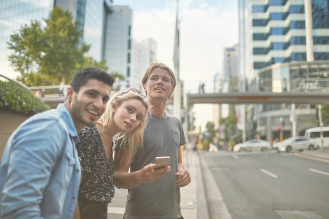 Three young people on a street in a new city using a phone where a hotel is marketing to millennials