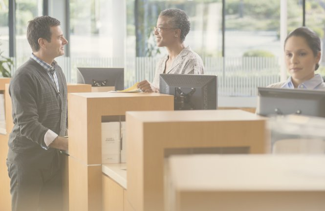 Bank employee with skills for finance jobs serving a customer at the counter