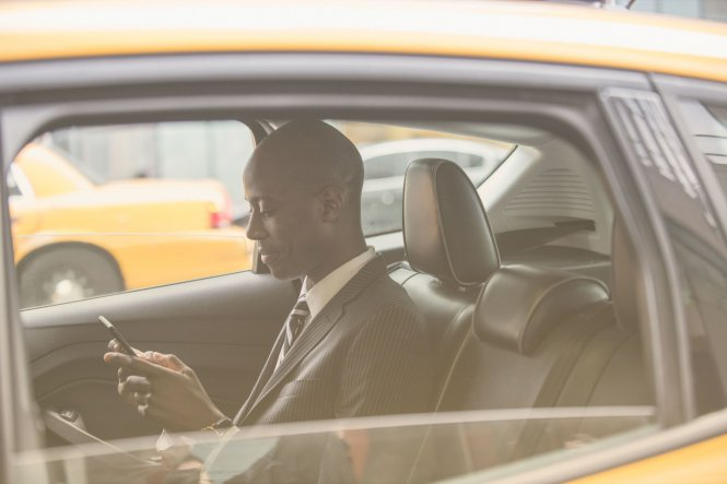 Person using mobile device in a taxi to access business files — UCaaS vs. VoIP