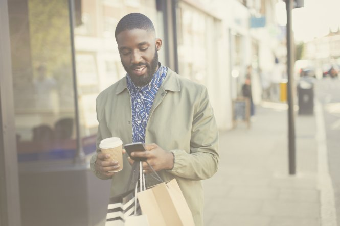Person walking down street with shopping bags, phone, and coffee — requirements of enterprise CPaaS