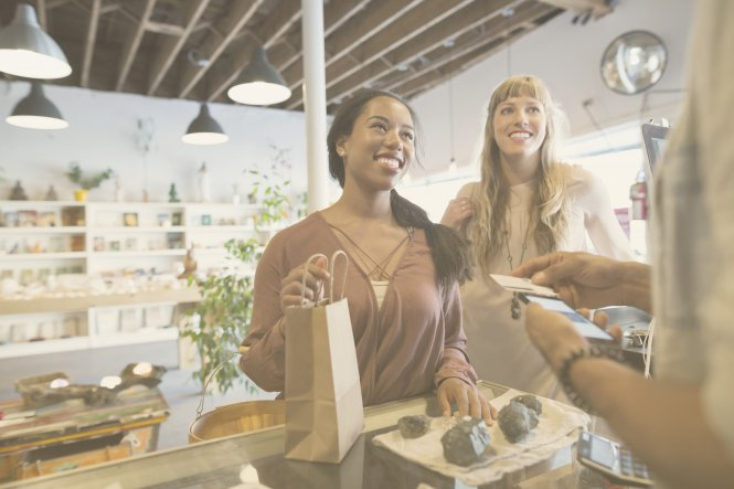 Retail employee providing personalized customer experience to two customers