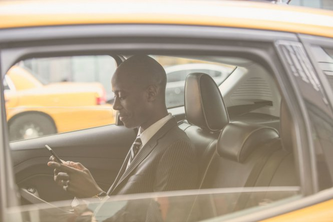 Businessperson in cab working on smartphone demonstrating mobile app use in business