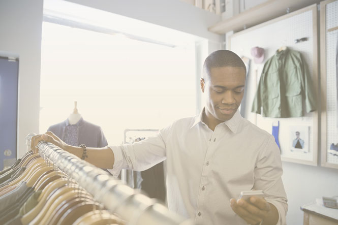 Business owner in a clothing store using SD-WAN solutions for retail organization via a smartphone