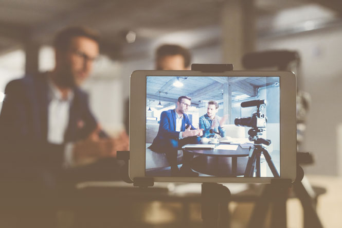 Two professionals talk to colleagues via a video conference app while a camera records them