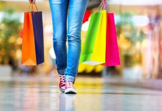 <p>Woman walks in a mall with multicolored shopping bags.</p>