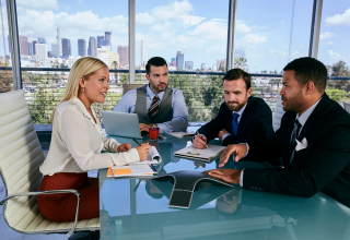 <p>Four people in an office, sitting at a desk and talking, with a business phone system in the foreground.</p>