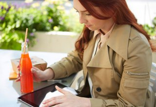 <p>A woman sitting at a table outside, drinking a soda and using a tablet.</p>