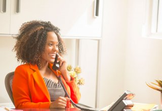 <p>Happy woman talks on the phone</p>