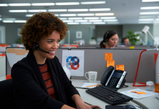 A smiling woman in an office, using a headset to speak on the telephone.