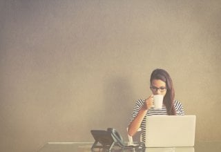 <p> A woman works from home and drinks coffee at a desk.</p>
