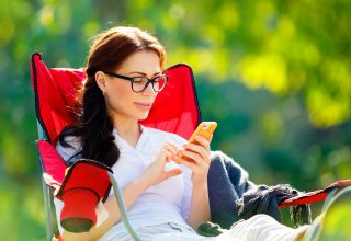 A woman using her smartphone from a lawn chair, highlighting one of the benefits of the cloud.
