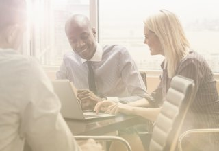 Employees, understanding cloud technology benefits, gather around a computer.