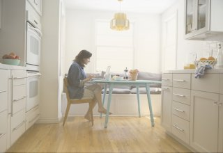 A woman using her kitchen as an office, because working from home benefits the environment.
