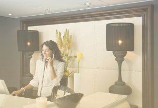 A woman talking on the phone at a reception desk, using SD-WAN solutions for quality of service.