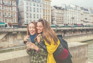 Two female travelers taking a selfie and enjoying their trip, courtesy of hotel API integration