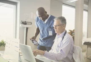 A male physician and male nurse discuss healthcare marketing solutions