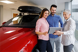 A car saleswoman uses car dealership mobility benefits on her tablet with a man and woman