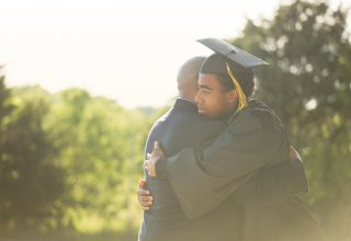 A young man who had an academic career enriched by mobile apps embraces his dad at graduation.