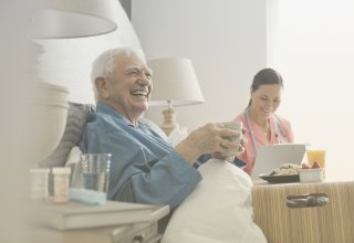 An elderly patient's caregiver uses patient care technology to communicate with a physician