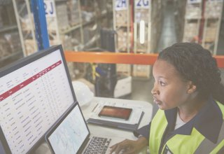 Employee in warehouse looking at data on screen representing manufacturing trends for 2019
