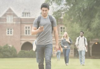 Student using flipped learning on smartphone and walking across campus with backpack on