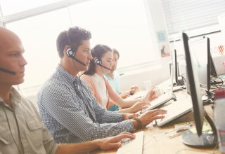 UCaaS and contact center agents with headsets taking customer calls at computer